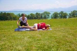 """Vorgeschmack auf unser Buch """"Mut zum neuen Knie!"""": eine Physio-Übung am Chiemsee mit Heidi Rauch als Patientin und der Manualtherapeutin Birgit Ferber-Busse."""